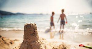 Kuva hiekkalinnasta ja kahdesta lapsesta rannalla