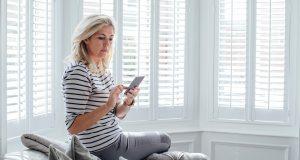 Nainen katsoo puhelimen näyttöä sohvan kulmalla.