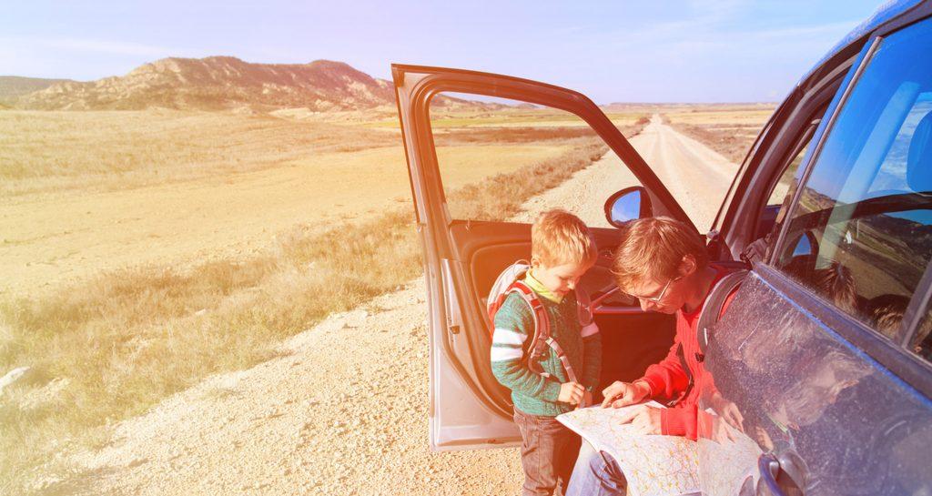 Mies ja poika tutkivat tiekarttaa automatkalla